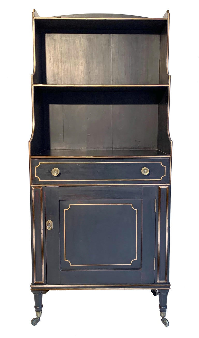 This elegant open bookcase and cabinet has been crafted out of ebonized beechwood and features gilt highlights. The feet stand on small brass wheels. It has retained its original brass handles.  The depth of this charming piece of furniture