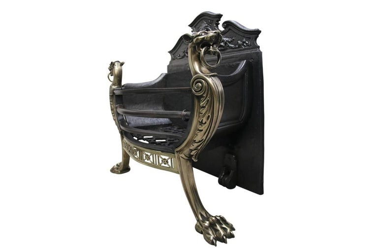 Mid Victorian dog grate in the Regency style supported by bronze wolfhounds with rings in their mouths, and on clawed feet, the brass apron is bowed and pierced. Dated 1884.
