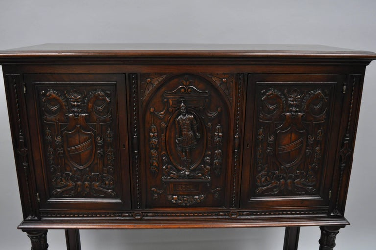 Antique Renaissance Revival figural carved walnut cabinet. Item features ornately carved walnut panels of shields and crests, horse heads, as well a central soldier. Cabinet has two swing doors, carved support columns, lower shelf, panel back, and