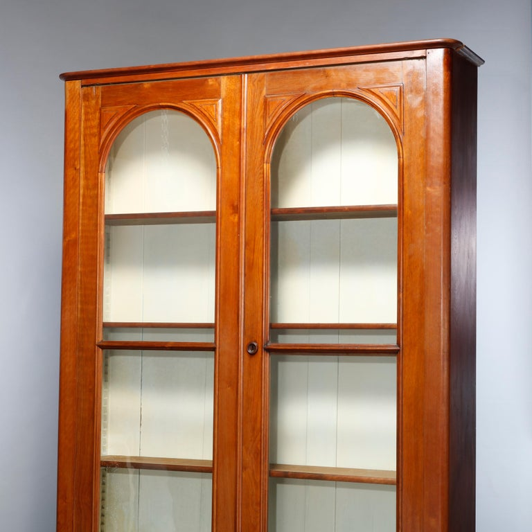 An antique Renaissance Revival bookcase offers walnut construction with double doors with arced glass windows over lower with drawers having carved pulls, c1880.    Measures: 92