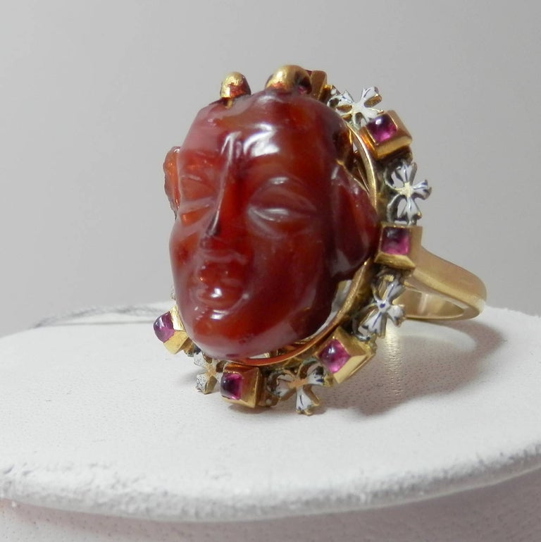 The center carving in agate is a 3 dimensional devil figure.  This carving is c. 1550.  It is set in an antique Holbeinesque ruby and enamel frame.  This frame dates to the mid-19th century.  The ring has been reinforced by adding a new gold shank.