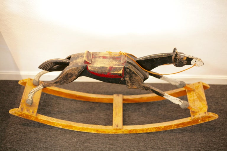 An antique black wooden rocking horse, circa 1900. In good vintage condition. Small chip to one of the front wooden boards. New leather reins.