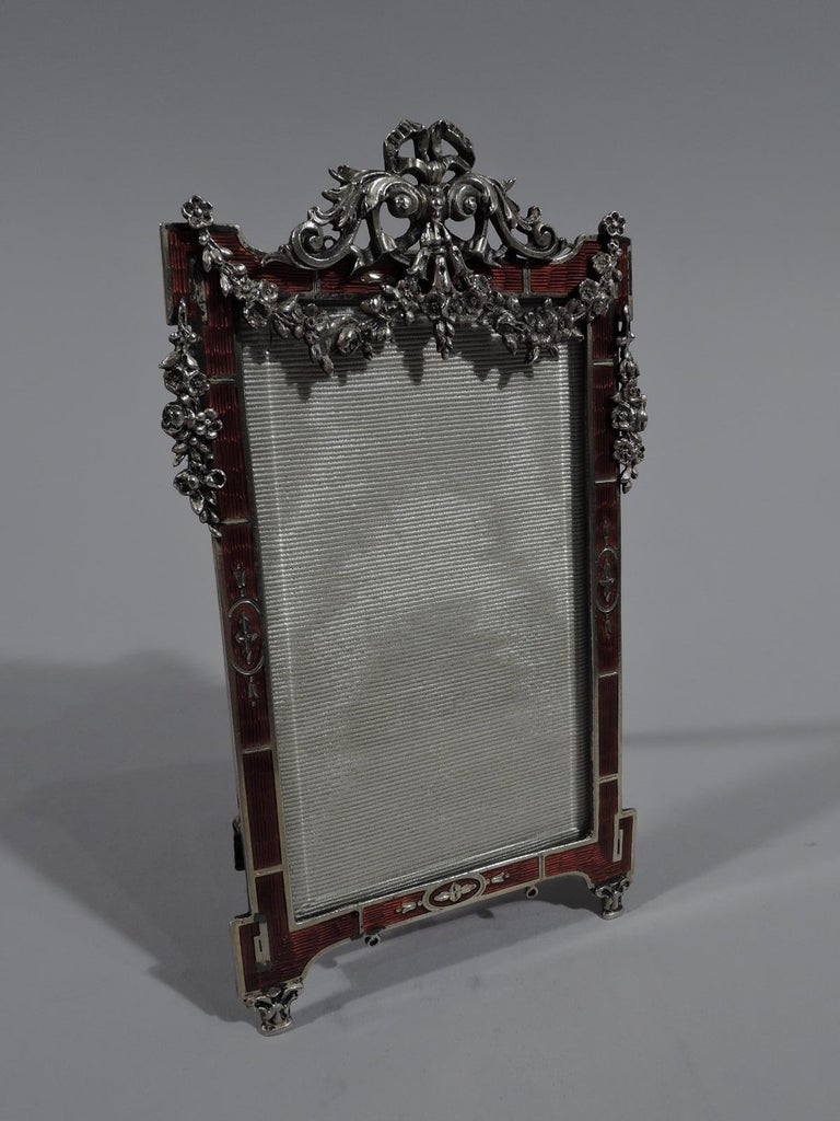 Rococo Revival silver and enamel picture frame, ca 1910. Rectangular window. Surround flat block volute corners. Dramatic red guilloche enamel and inlaid stylized leaves. Applied ribbon and leaf crown with overhanging flower garland. Two capital