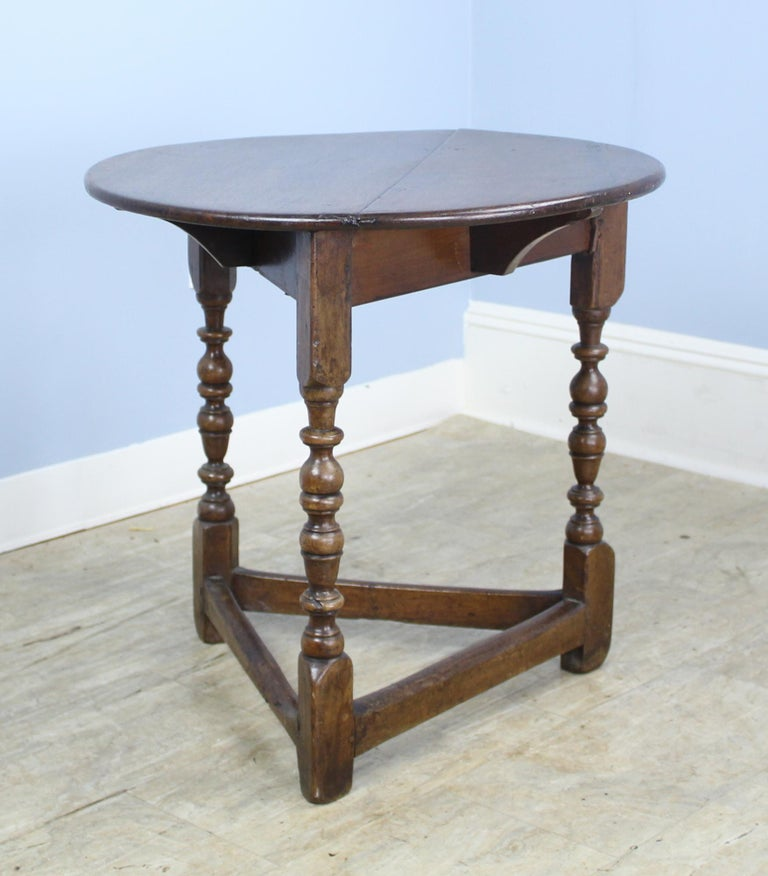 An early lamp or side table with turned legs and wonderful color and patina. Interesting wear on the stretchers as well as on the top. Note that the top is not a perfect circle.
