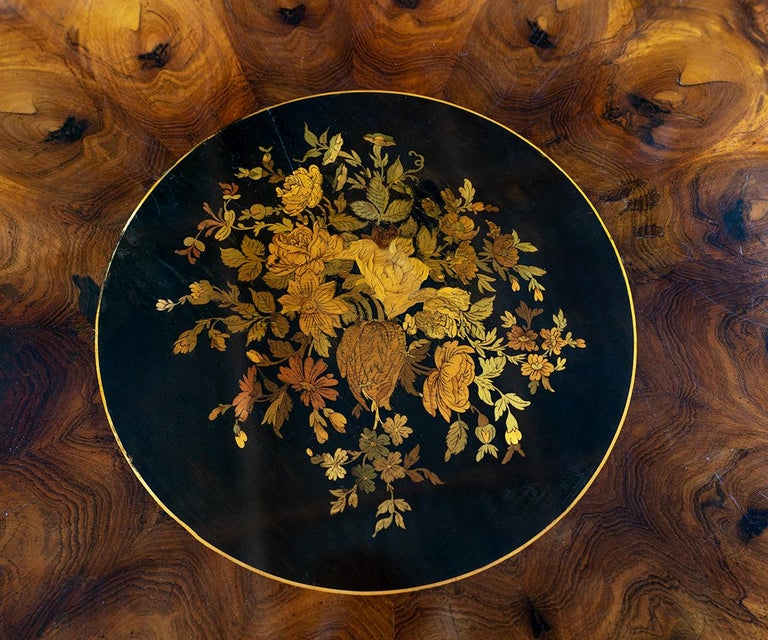 Offered is this fine antique round table with excellent quality marquetry using walnut and rosewood accents featuring a bouquet of colored leaves and flowers in the center. Each of the colors of the flowers and leaves are actually a different