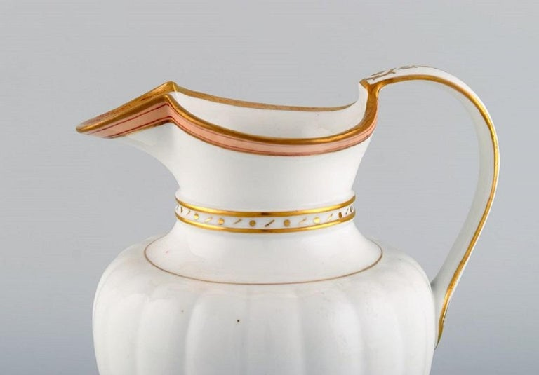 Antique Royal Copenhagen chocolate pot in hand painted porcelain with pink ribbon and gold decoration. Dated 1820-1850. Measures: 22 x 20 cm. In excellent condition. Stamped.