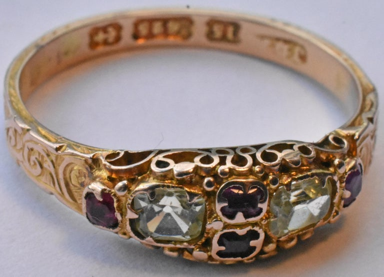 Lovely 15k early Victorian ring with two cushion cut chrysoberyls and four rubies, hallmarked Birmingham and dated 1868. Swirls, whorls and curlicues engraved along the band add interest and texture. Rubies are enclosed in a cloverleaf shaped