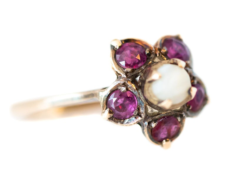 Antique Circa 1880 Ruby and Pearl Floral Ring - 18 Karat Yellow Gold, Rubies, Pearl  Features: Floral Design Round Pearl Center 5 pinkish red Round Ruby-set petals 18 Karat Yellow Gold, with a light patina Elevated setting with Open Back Prong set