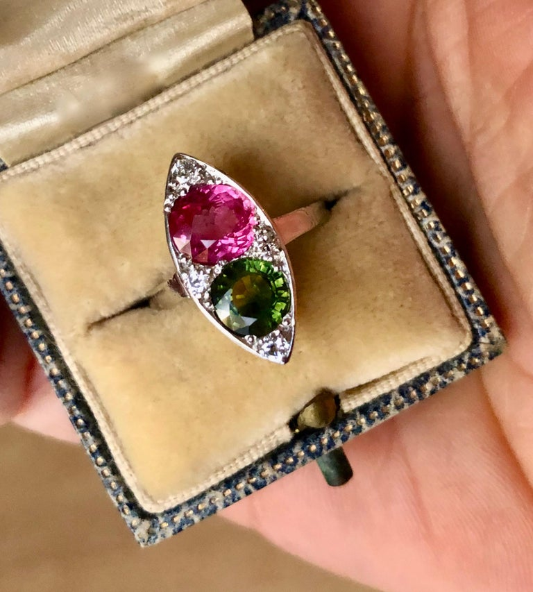 An Antique Style Ruby and Sapphire Platinum Navette Ring Inspire on the Art Deco Era. Navette The ring is accented with one, round cut pinkish red natural ruby, one round cut green natural sapphire and four, bead set, round single cut white