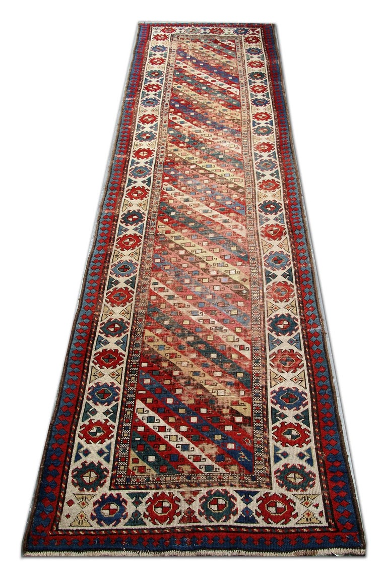 Handmade carpet oriental rug born out of nomadic traditions, this antique striped rug from Ganjeh features a spectacular array of modular stripes and classical border motifs that have a graphic large rugs linear style. The warm, earthy field is