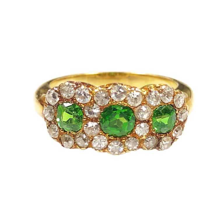 Circa 1900 14K Yellow Gold Ladies Ring, measuring 3/4 X 5/16 inch, set with 3 Cushion cut Fine Color Ural Demantoid Garnets. Surrounded by Old European cut Diamonds totaling 1 Carat. Finger size 6 1/2.  Excellent, near unworn condition.