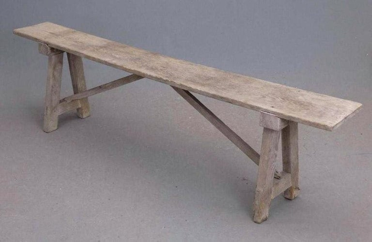 The antique rustic country pine bench is constructed of a flat seat supported by a pair of splayed legs and two braces. the pieces are grooved and nailed together for sturdy construction. Perfect for the mud room, at the back door or at a picnic