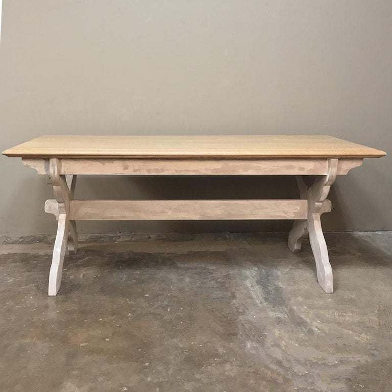 Antique Rustic Country French Whitewashed Trestle table was hand painted with Old World finishes. The layers of waxed patina compliment the natural beauty of the wood top and distressed whitewashed trestle base. The X-shaped leg supports were given