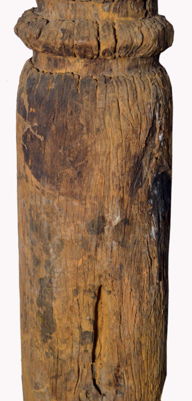 A 19th century rustic hand-carved Thai pole from the mountainous city of Chiang Mai, featuring a natural patina. Born in northern Thailand, this pole adopts a cylindrical shape and stands on two legs. The top features a baluster detail and two round