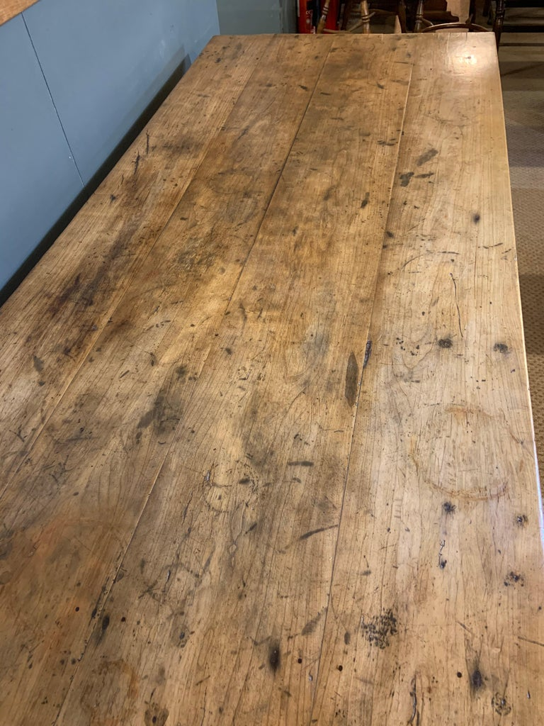 Antique rustic wide pale cherry farmhouse table with a four plank top and tapered legs.