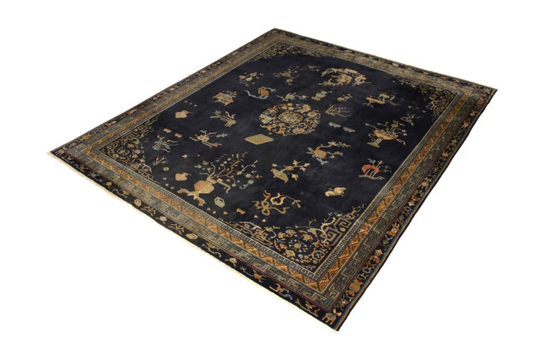 Hand knotted in wool originating from India circa 1920, this antique art deco rug connotes a Samarkand rug design, inspired by neighboring Peking rugs with a unique colloquial take. A regal play of navy blue and gold hues both inspires a classic