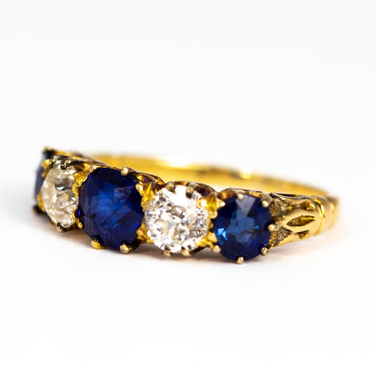 The sapphires in this ring are a deep and gorgeous blue colour. The central stone measures 60pts and the outer measure approximately 40pts each. The old mine cut diamonds which sit in between are a G/H colour VSI. The stones are all modelled in 18ct