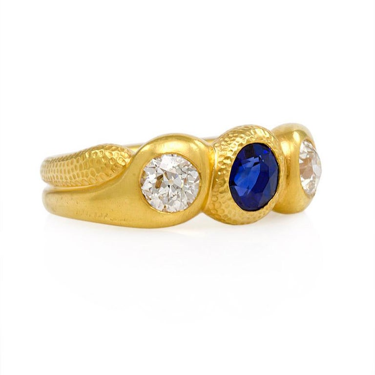 An antique gold stylized and textured three-stone gypsy ring set with a faceted oval cut sapphire flanked by Old European cut diamonds, in 18k.  Signed W.M.  Atw diamonds 0.98 ct.  Top measures approximately 20mm across finger Current size: US 7 3/4
