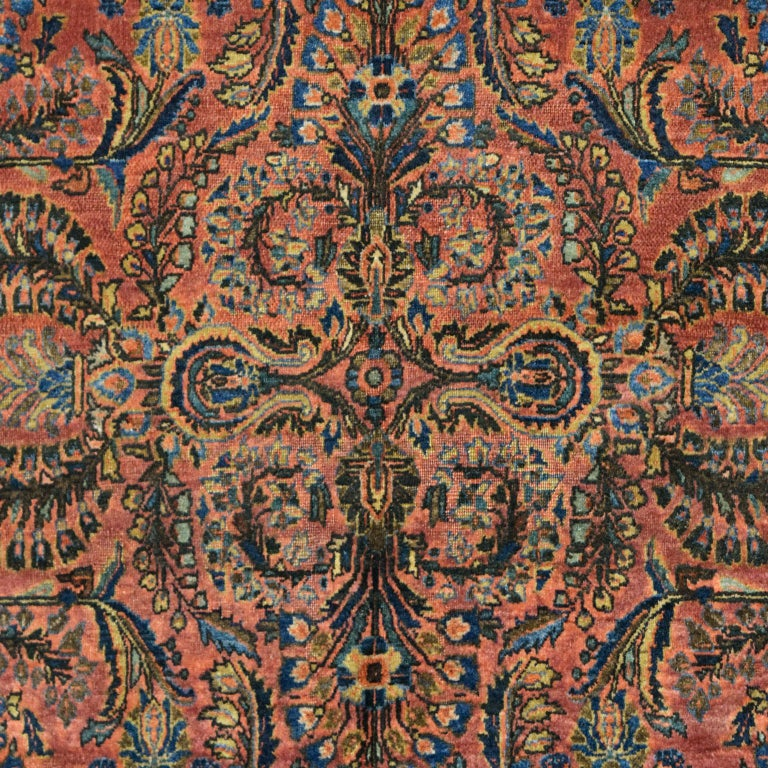 """Woven in Iran, this hand-knotted Sarouk carpet measures 4' x 6'5"""" and belongs to the Antique Collection. Crafted using a traditional Persian weave, this antique Sarouk has a soft pile and a durable foundation. The carpet's rich red background, along"""