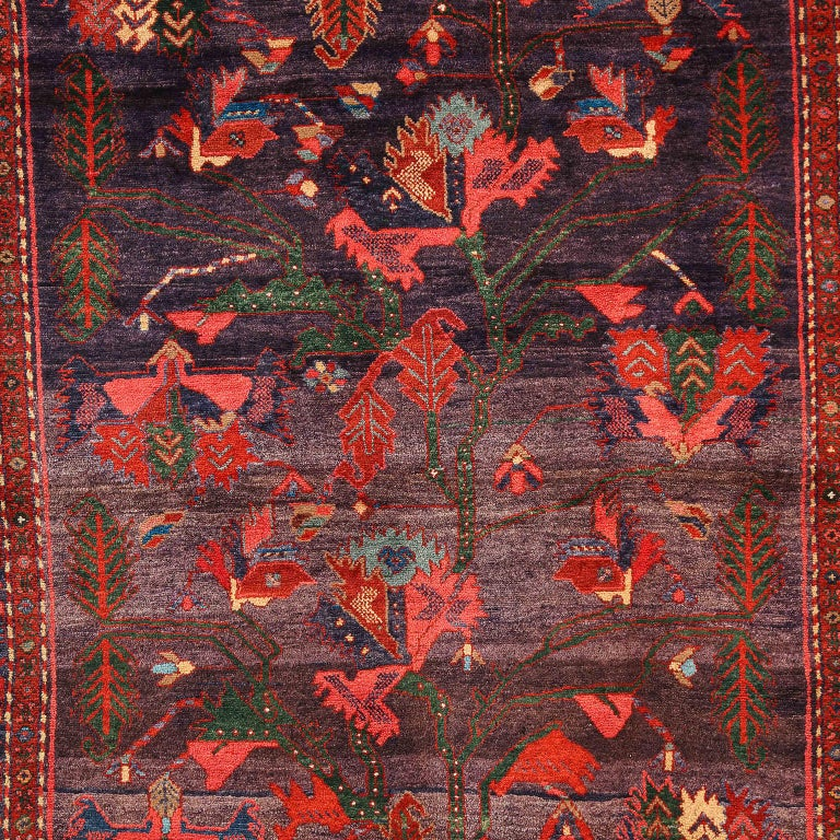 This antique Saveh Persian carpet in pure wool and vegetable dyes circa 1910 features a unique tree of life composition with an overall field design and multi-layered border. Intricate motifs including morning doves, botehs, and cypress trees