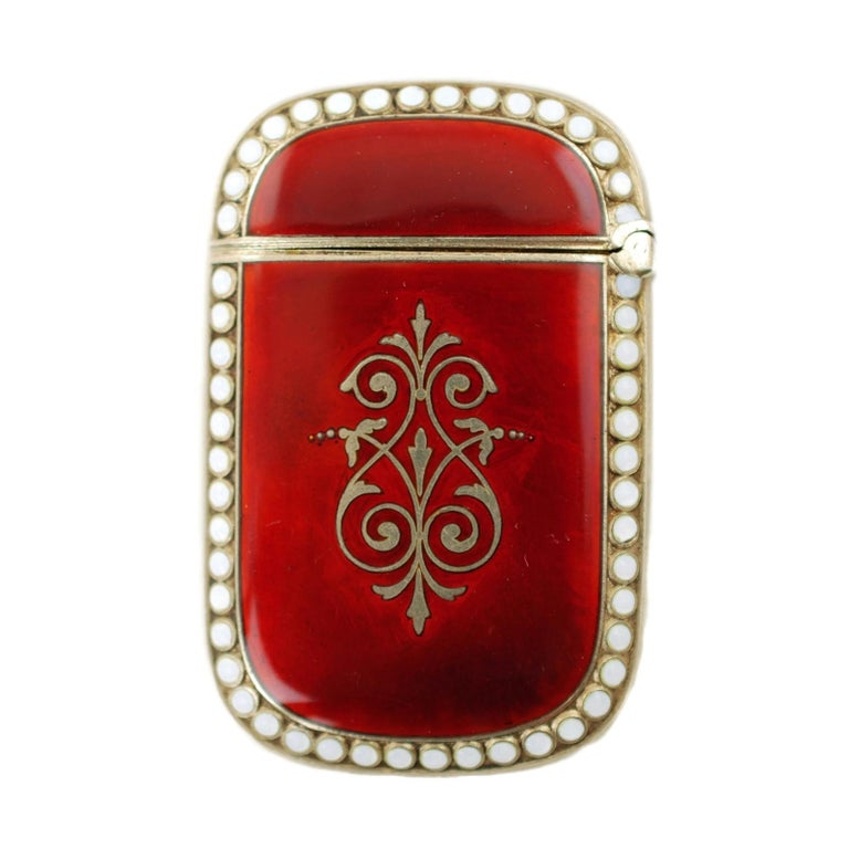 This highly collectible circa 1896 vesta case was made in Oslo, Norway by Arthur David-Andersen. The match safe has a hinged lid and is composed of sterling silver with a vermeil wash. The exterior features crimson enamel decoration with large,