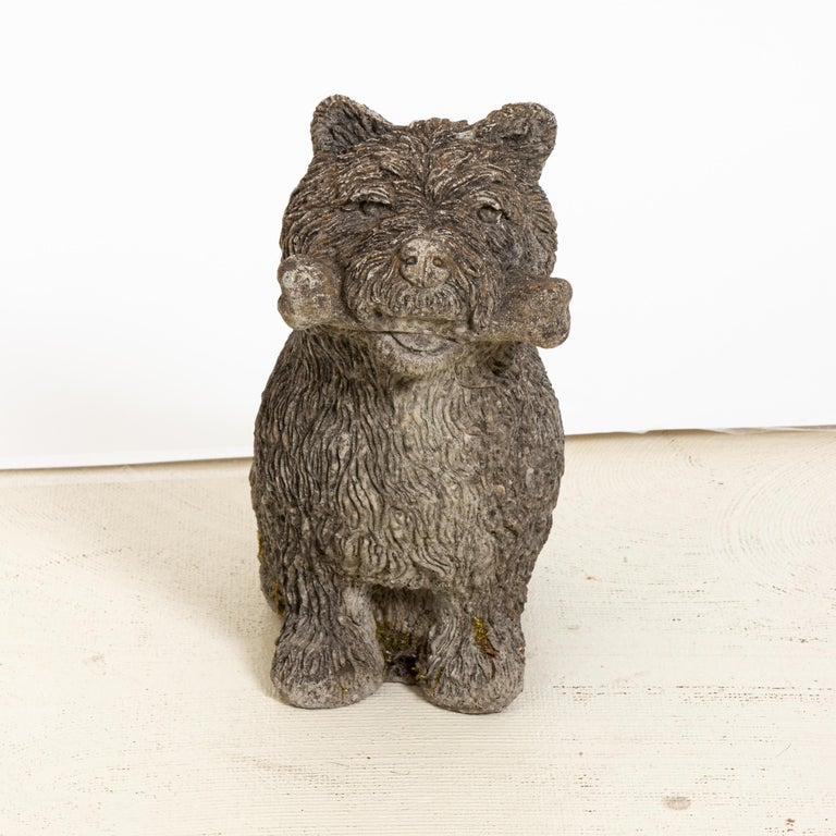 Unique cast stone garden statue in the shape of a Scottie dog holding a bone. Made in England in the early 20th century, this charming statue a playful element to add to the landscape. Good condition, weathered with age and exposure to the elements.
