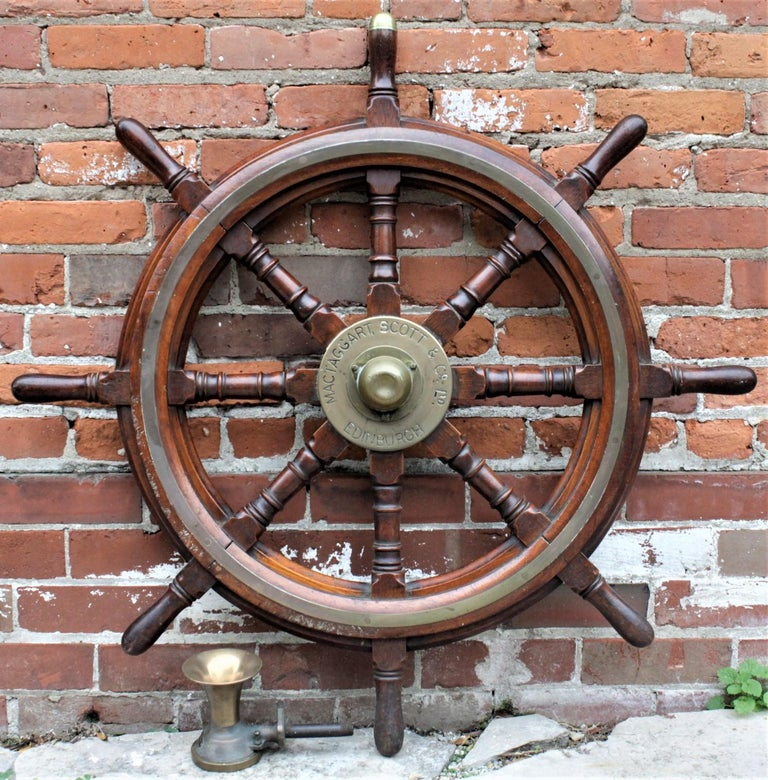 This antique nautical pairing consists of an antique solid mahogany ship's wheel made by the Mactaggart Scott & Co. of Edenborough Scotland in circa 1900 and a more recent brass air Horn or whistle made in the United States in circa 1920. The ship's