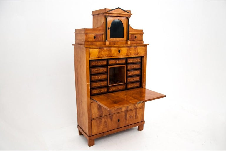 The unique, birch secretary was created circa 1820 in Scandinavia. Empire style furniture has numerous drawers and storage compartments, the hinged flap opens as a desk top. The secretary is decorated with a subtle black tortie band - unique.