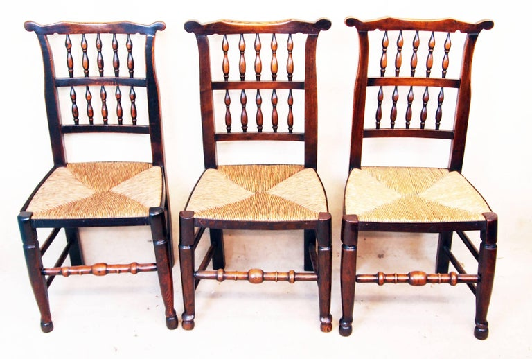 A very attractive matched set of eight (six single and two arm) early 19th century ash and elm spindle back dining chairs having rush seats in good order raised on elegant turned legs and stretchers,  circa 1800.  Measures: Height 37in