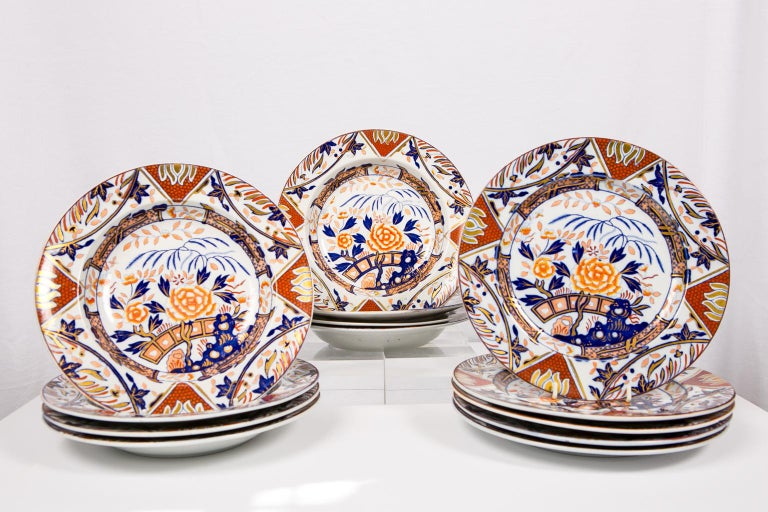 An extensive set of English Imari dishes painted in iron red, deep blue, and gold showing a 