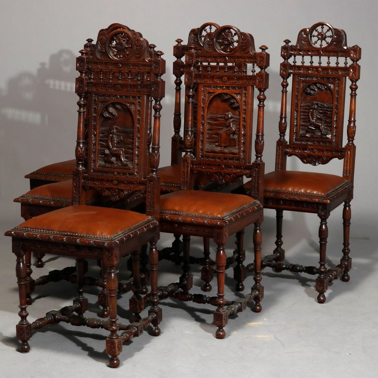 An antique set of six continental dining chairs offers oak construction with wagon wheel form crest surmounting spindled and deeply carved backs with arch reserve having genre scenes with figures and countryside elements over leather seats, raised