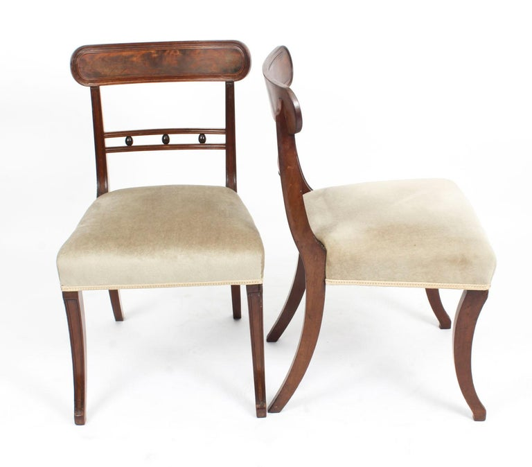 This is a beautiful set of six English antique Regency flame mahogany sabre leg dining chairs, circa 1870 in date.