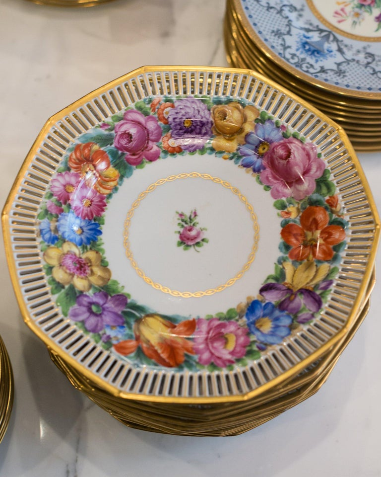 An ornate set of 12 antique Dresden gold and floral dinner plates produced between 1901-1914. What makes these so special is the elaborate incised gallery edge. Franziska Hirsch started her porcelain painting business in Dresden in 1893. The studio