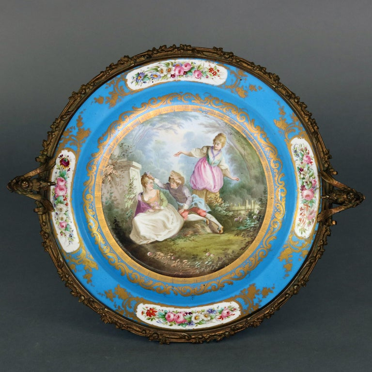 An antique Sevres School porcelain pictorial charger features hand painted central courting scene in countryside setting and having Sevres signature gilt decorated blue rim having floral reserves, seated in floral and foliate form double handle
