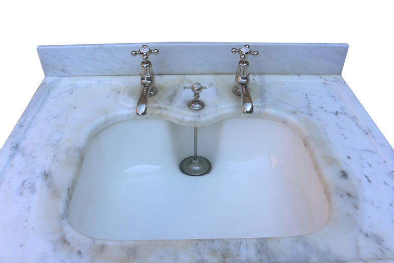 The basin has been resurfaced and is in excellent condition. Nickel-plated legs, taps and plunger waste. Carrara marble. Measures: Height 78 cm (to the basin) 87 cm (to the splash back) Weight 48 kg.