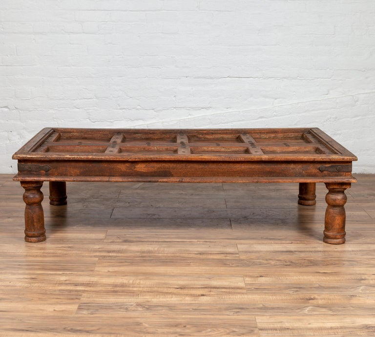 An antique Indian palace door made into a coffee table with sheesham wood and iron studs. Born in India during the early years of the 20th century, this charming palace door has been made into a coffee table. The top, presenting a succession of