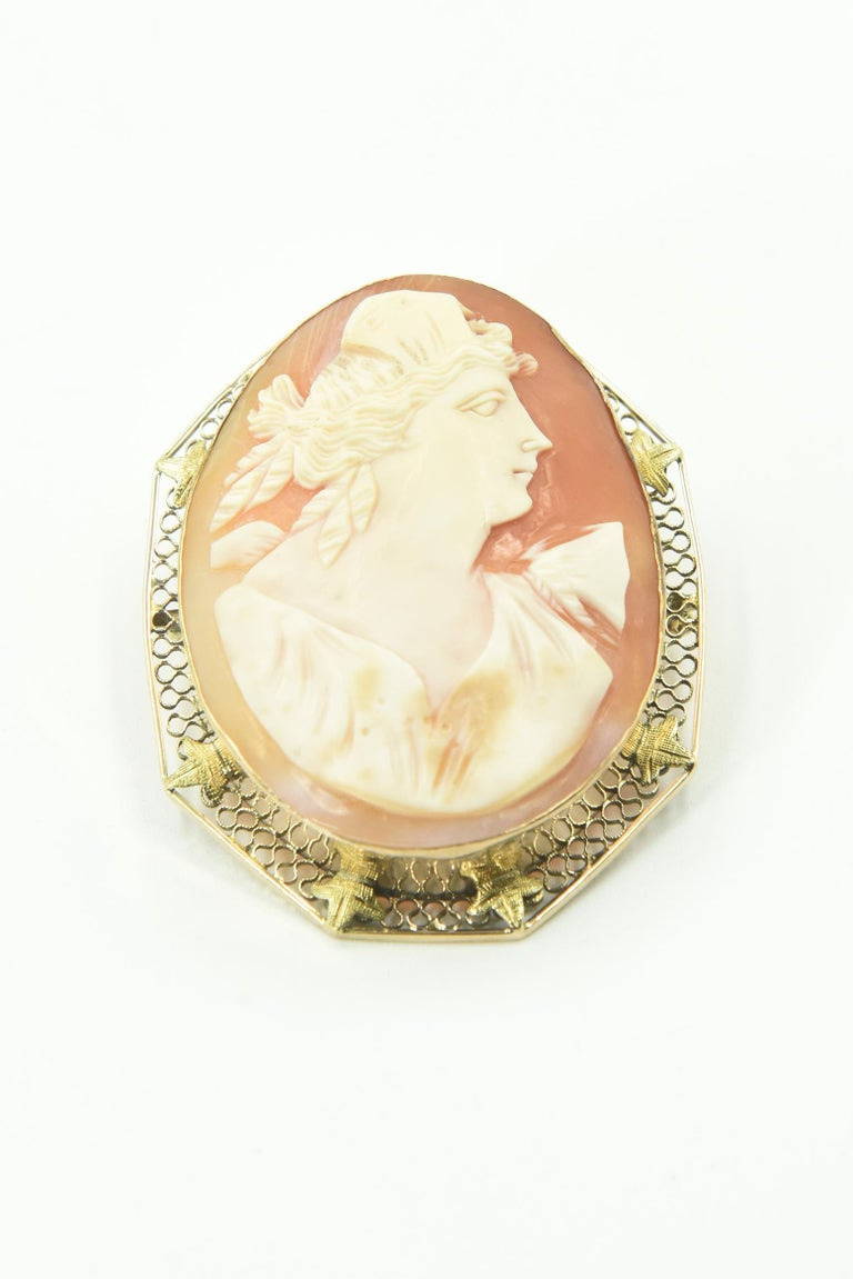 Victorian shell cameo Roman woman portrait hand carved & mounted into a 14k gold brooch pendant.  The frame work is traditional filigree, with lovely, detailed leaves surrounding the solid bezel frame. The cameo itself is perfectly carved, a lady in