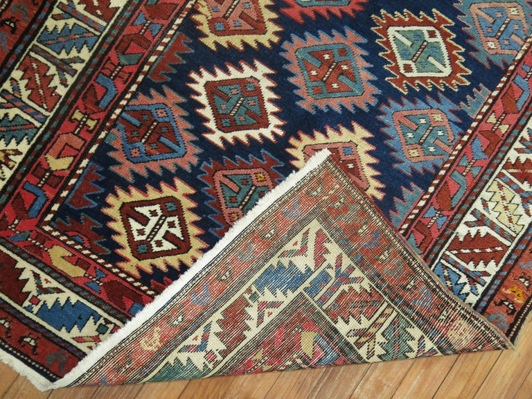 A geometric tribal looking Caucasian Shirvan rug from the early 20th century. Colorful geometric design on a navy blue field.