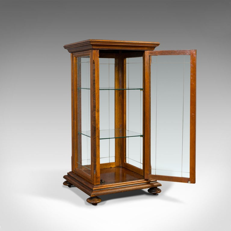 This is an antique shop display cabinet. An English, oak and walnut showcase, dating to the Edwardian period, circa 1910.  Beautifully glazed cabinet Displays a desirable aged patina Oak shows fine grain interest and pleasing caramel