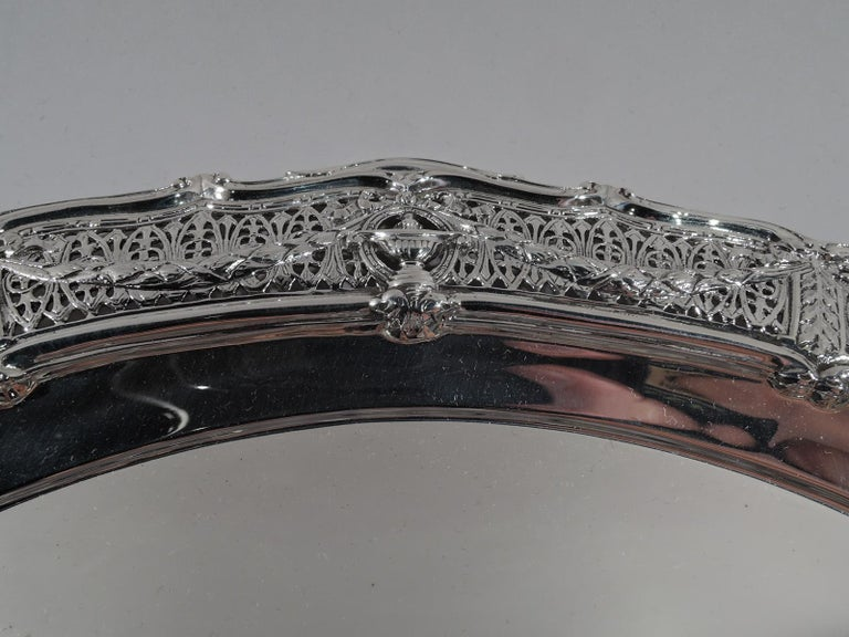 Edwardian Regency sterling silver tray in Adam. Made by Shreve & Co. in San Francisco, circa 1910. Plain well and wide shoulder with classical vases overlapping rondels joined by leaf swags on pierced fern ground. Ogee scroll rim. Fully marked and