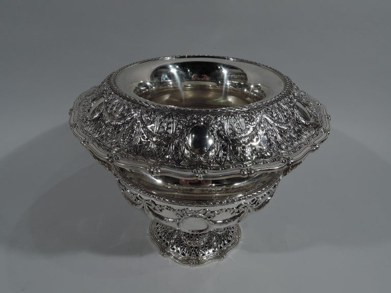 Edwardian Regency sterling silver wine cooler in Adam pattern. Made by Shreve & Co. in San Francisco, ca 1915. Bellied bowl, inset concave neck, turned-down and scrolled rim, and domed and scrolled foot. Leaf-capped and wrapped high-looping side