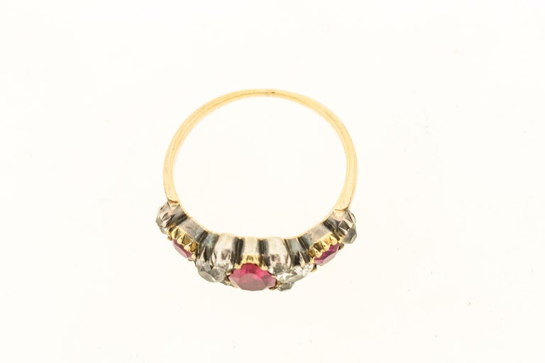 A late Georgian silver topped 18k yellow gold ruby and diamond ring, circa 1840. The ring centers on a pear shape ruby with bright red color. It has six old mine cut diamonds around it, and then two more rubies and two more diamonds. The pear shape