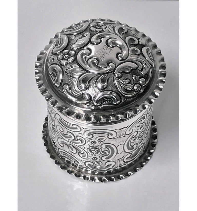Antique silver caddy box, London 1898, Mappin & Webb. The cylindrical container on crimped base border, the body richly decorated with embossed foliage against stippled background, the cover of dome form conforming in decoration, centering cartouche