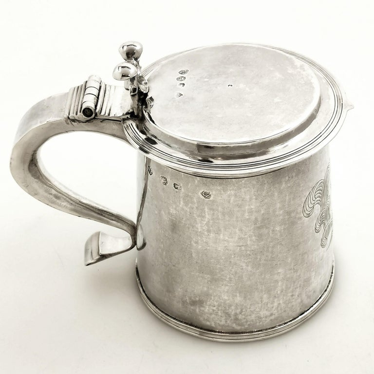 A magnificent Antique Charles II sterling Silver Lidded Tankard. This Tankard has a slight tapered straight sided form with a hinged flat lid. The Tankard features a large engraved crest opposite a substantial scroll handle and a shaped thumb piece