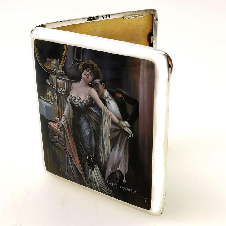A magnificent Antique solid Silver Cigarette Case with a beautiful Enamelled cover signed by Luis Usabal. The image on the cover of the Case shows a couple in an embrace wearing evening wear in a detailed dining room setting. This image is created