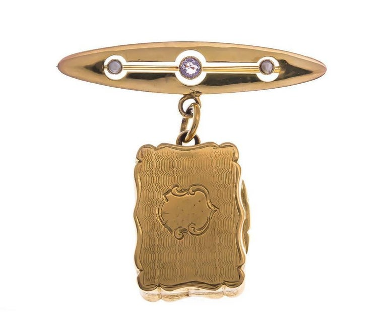 GEMMOLOGIST'S NOTES This beautifully crafted Locket Brooch.. a gorgeous piece that's the perfect accessory for your light jacket or coat.  Designed with an amethyst and split pearl brooch, that beautifully suspends an ornate rectangular locket. A