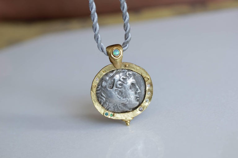 In stock. Antique silver Macedonian Coin Medallion Pendant. Antique 3rd Cent BC Greek coin pendant, set in 21k gold bezel, embellished with small diamonds and garnet accents. The Bail is highlighted with Lightning Ridge Opal, also set in a