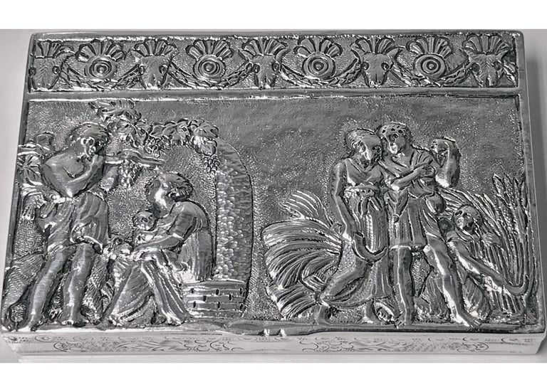Antique Silver hand chased box, Continental circa 1900. The box of rectangular shape, the hinged cover with raised decorative depictions of men, women, children and animals in landscape scenes against stippled background; the sides with engraved