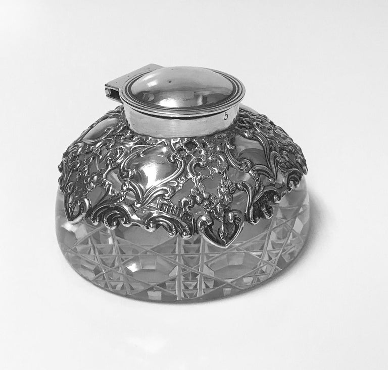 Antique silver and glass inkwell paperweight, Birmingham, 1900 H. Matthews. The inkwell with pierced foliage and vacant cartouche silver decoration, plain hinged thread surround cover all on plain glass body with unusual octagonal and diamond square