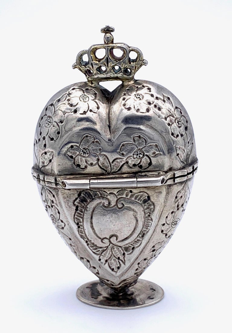 Charming silver box in the shape of a  heart with a crown. The heart is on all sides decorated with engraved flowers. The inside of the box is guilded.